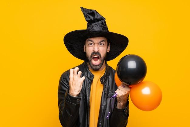 Mens die met heksenhoed zwarte en oranje luchtballons voor halloween-partij houdt gefrustreerd door een slechte situatie