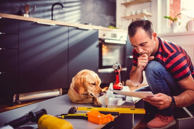 Mens die met hond blauwdrukken controleert terwijl het bouwen van keukenkasten
