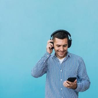 Mens die met hoofdtelefoons smartphone bekijkt