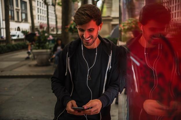 Mens die met hoofdtelefoons terwijl het bekijken smartphone glimlacht