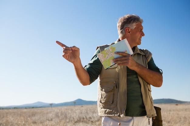 Mens die met kaart terwijl status op landschap richt