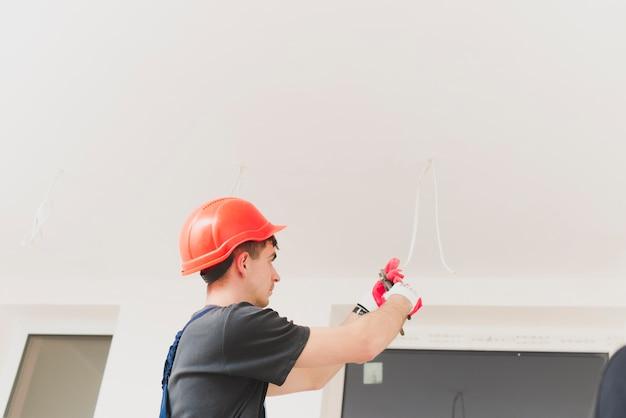 Mens die met kabels bij plafond werkt