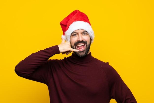 Mens die met kerstmishoed over geïsoleerde gele achtergrond telefoongebaar maakt. bel me terug teken