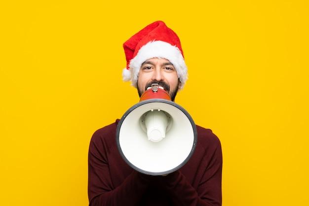 Mens die met kerstmishoed over geïsoleerde gele muur door een megafoon schreeuwt