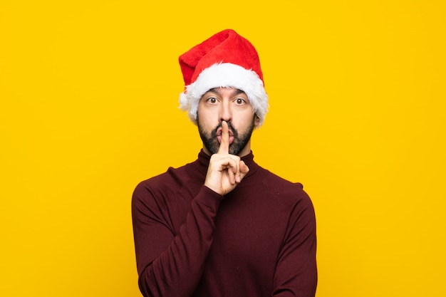 Mens die met kerstmishoed over geïsoleerde gele muur een teken van stiltegebaar toont dat vinger in mond zet