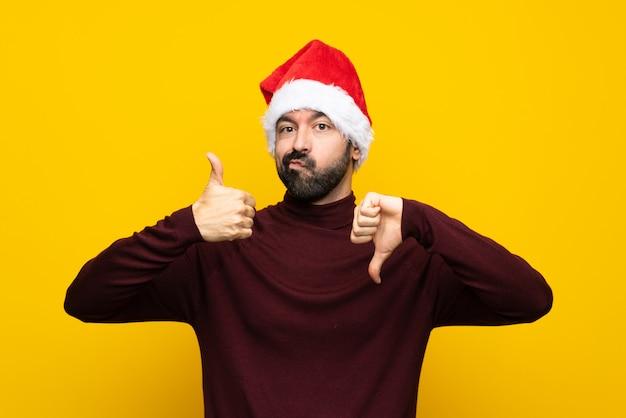 Mens die met kerstmishoed over geïsoleerde gele muur goed slecht teken maakt. onbeslist tussen ja of niet