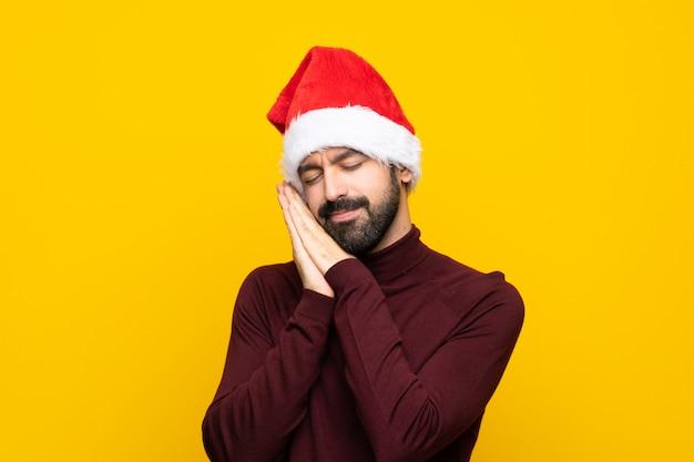 Mens die met kerstmishoed over geïsoleerde gele muur slaapgebaar in aanbiddelijke uitdrukking maken