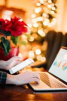 Mens die met laptop aan kerstmisseizoen werkt