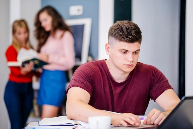 Mens die met laptop bij bureau bestudeert