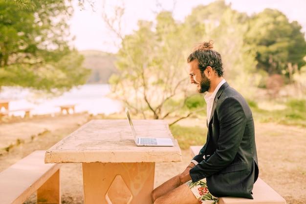 Mens die met laptop in zonnig park werkt