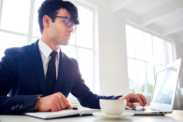 Mens die met laptop op kantoor werkt