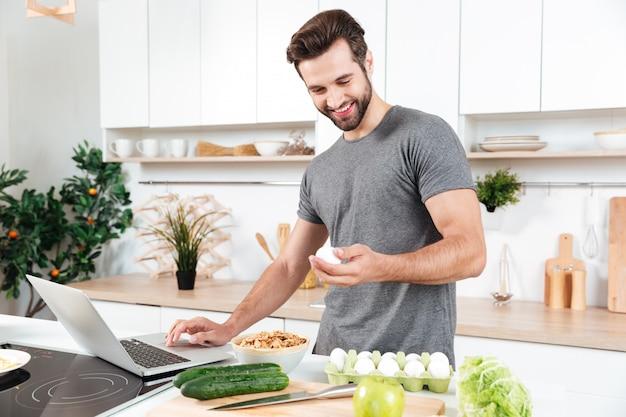 Mens die met laptop voedsel voorbereidt bij de keuken