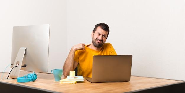Mens die met laptot in een bureau met vermoeide en zieke uitdrukking werkt