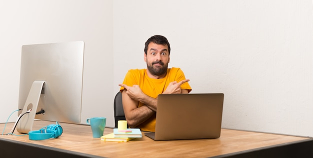 Mens die met laptot in een bureau werkt dat aan de zijtakken wijst die twijfels hebben