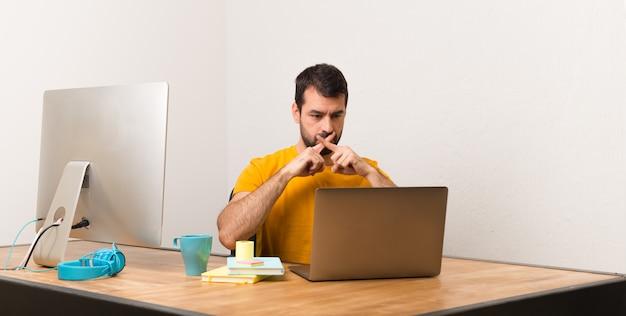 Mens die met laptot in een bureau werkt dat een teken van stiltegebaar toont
