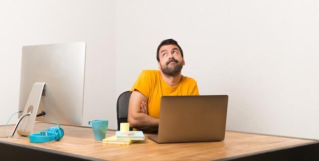 Mens die met laptot in een bureau werkt dat twijfelsgebaar maakt terwijl het opheffen van de schouders
