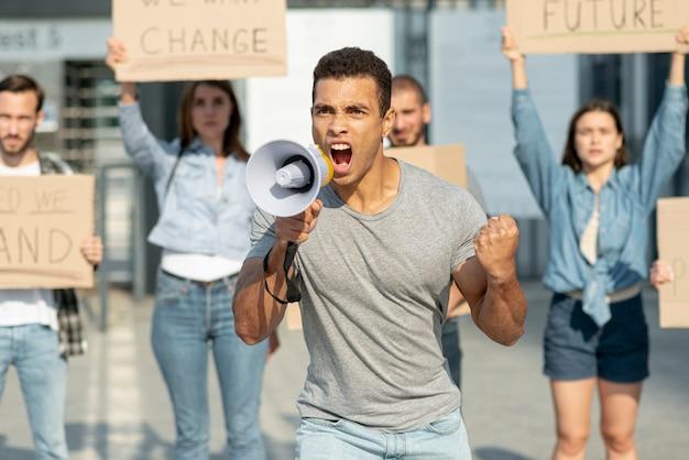 Mens die met megafoon met erachter activist protesteert