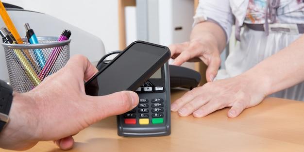 Mens die met mobiele telefoon in winkel betaalt