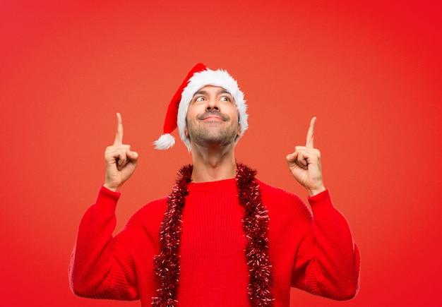 Mens die met rode kleren de kerstmisvakantie viert die met de wijsvinger richt