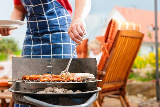 Mens die met schort worsten op barbecuegrill voorbereidt