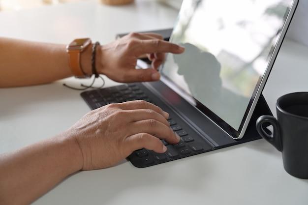 Mens die met tablet aan bureau werkt.