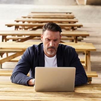 Mens die met zijn computer in openlucht werkt