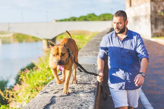Mens die met zijn hond loopt.