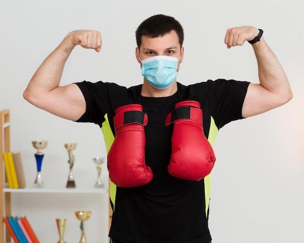 Mens die met zijn spieren pronkt terwijl het dragen van een medisch masker