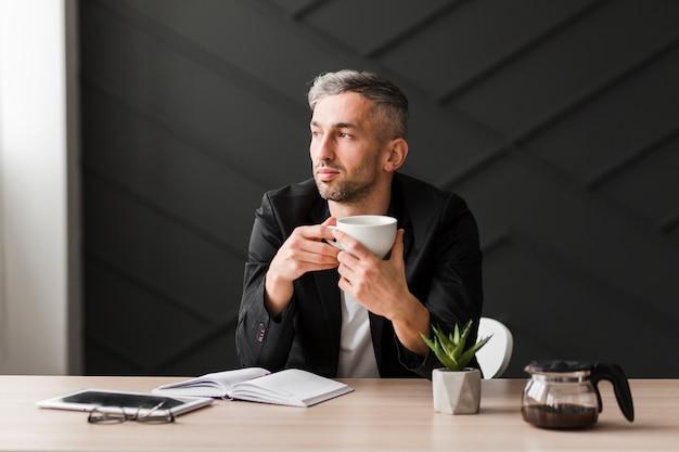 Mens die met zwart jasje zijdelings zittend zijn bureau bekijkt