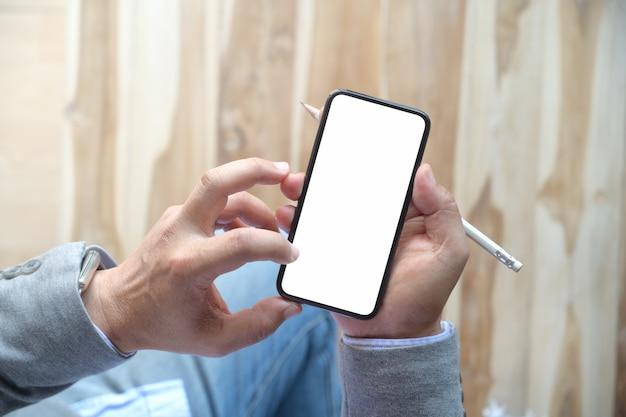 Mens die mobiele smartphone met behulp van bij houten lijst