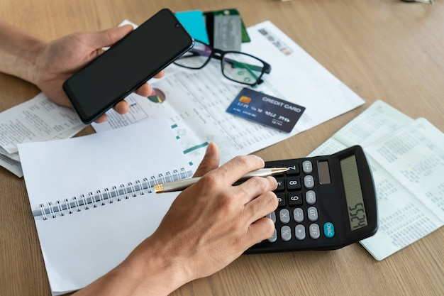Mens die mobiele telefoon houdt en calcutor, rekening en het concept van de besparing gebruikt