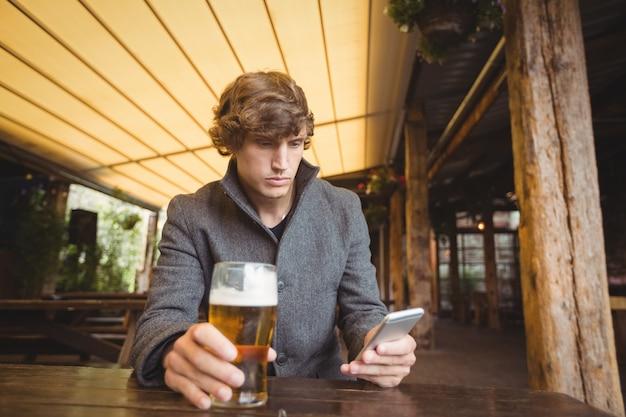Mens die mobiele telefoon met behulp van terwijl het hebben van glas bier