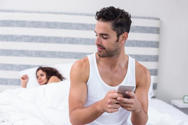 Mens die mobiele telefoon met behulp van terwijl vrouwenslaap op bed