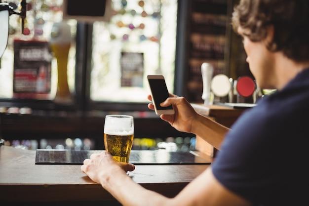 Mens die mobiele telefoon met in hand glas bier met behulp van