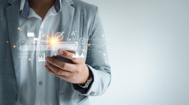 Mens die mobiele telefoontechnologie gebruikt voor digitale marketing van darts die op het doelwit zijn gericht. bedrijfsbeheer doelstrategie en actieplan. wereldwijde klantnetwerkverbinding op virtuele interface.