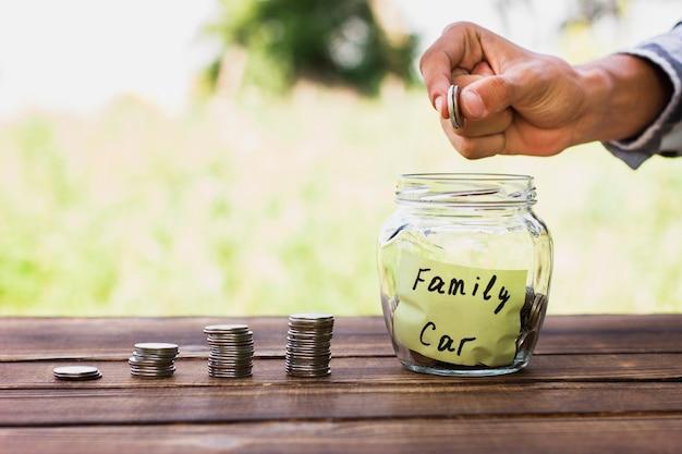 Mens die muntstukken in kruik met besparingen toevoegt
