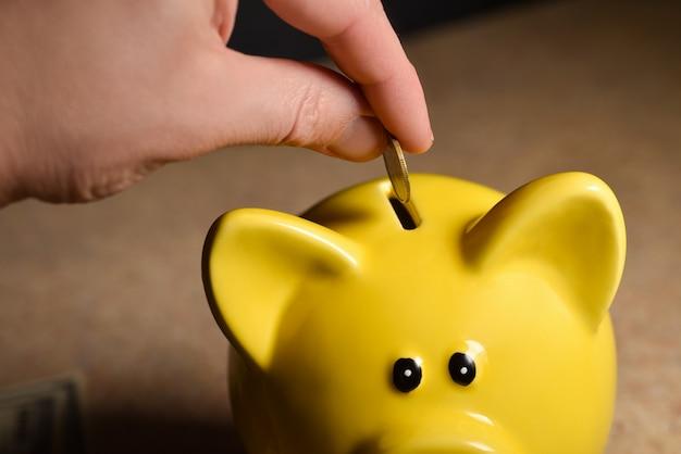Mens die muntstukken werpt in een piggy geel spaarvarken