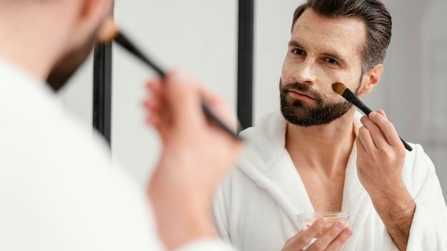 Mens die natuurlijke ingrediënten gebruikt voor een gezichtsmasker