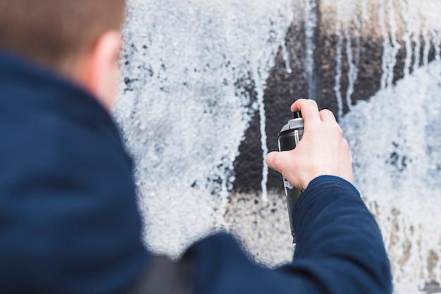 Mens die nevel gebruikt voor het trekken van graffiti op muur