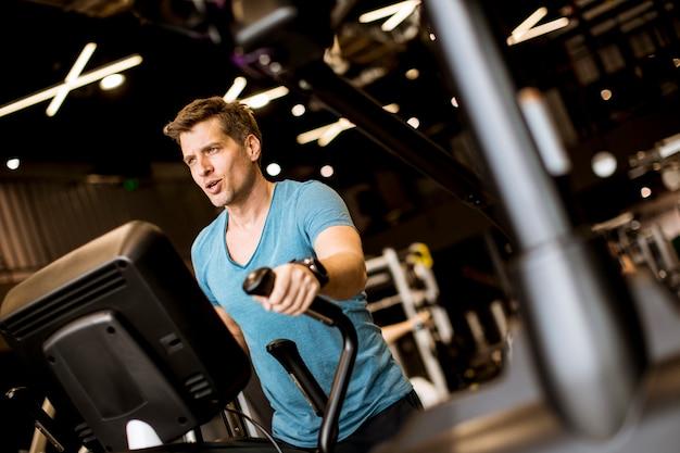 Mens die oefening op elliptische dwarstrainer in sportfitness gymnastiekclub doet