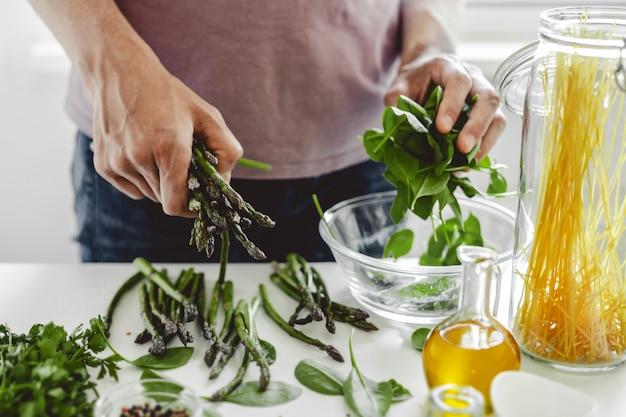 Mens die of asperge en spinazie voor thuis diner kookt voorbereidt. schoon eten.