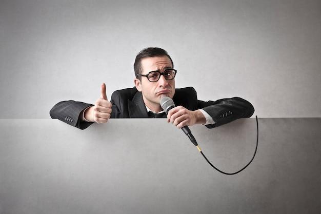 Mens die ok toont en een microfoon houdt