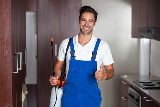 Mens die ongediertebestrijding in keuken doet