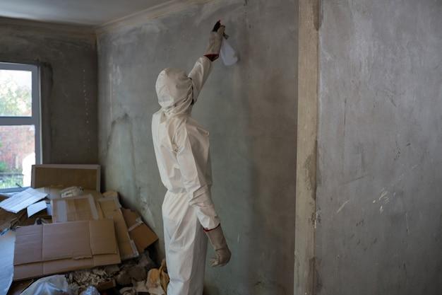Mens die ongediertebestrijding op een muur doet