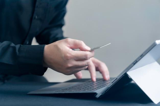 Mens die online door creditcard met digitale tablet of computerlaptop, internet-bankwezen of elektronische handelconcept betalen