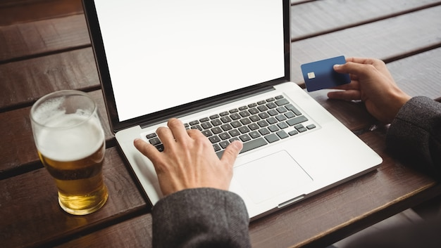 Mens die online het winkelen met creditcard op laptop doet