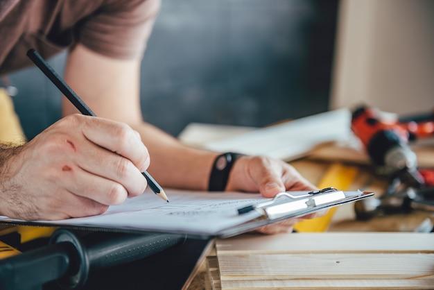 Mens die ontwerpplan met potlood op de lijst maakt