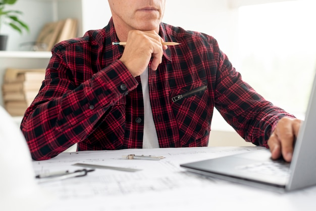 Mens die op architecturaal project op laptop kijkt