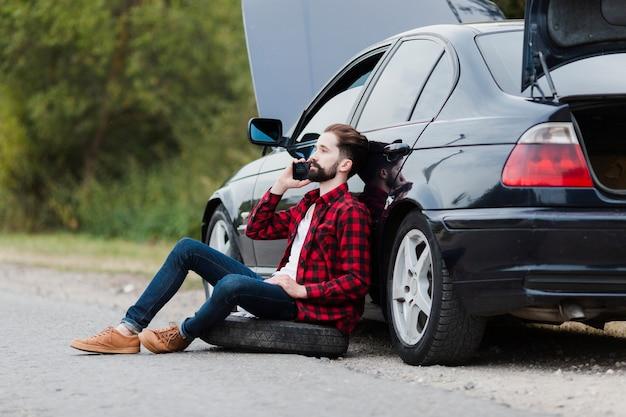 Mens die op auto leunt en op telefoon spreekt