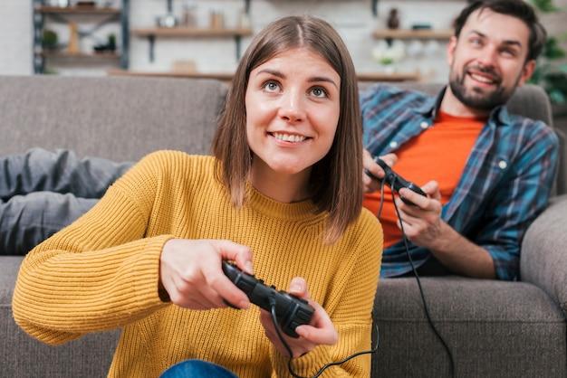 Mens die op bank het spelen videospelletje met zijn vrouw ligt